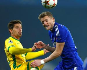 Sporting's Adrien Silva (L) challenges Chelsea's Andre Schurrle during their Champions League...