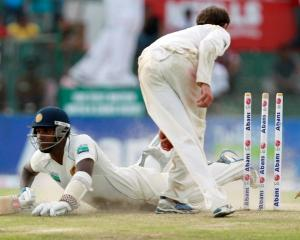 Sri Lanka's Angelo Mathews dives to complete a run as Australia's Nathan Lyon breaks the wickets...
