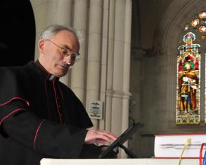 St Joseph's Cathedral priest Monsignor John Harrison accesses material on an iPad lying next to...
