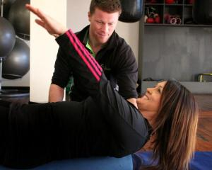 Christine stretches out under the watchful eye of Damian Keen at Let's Go Fitness. Photo by...