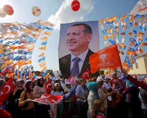 Supporters hold a poster of Turkish Prime Minister Tayyip Erdogan during a mass rally in Istanbul...