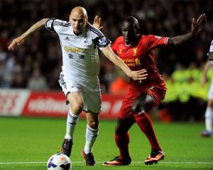 Swansea City's Jonjo Shelvey (L) passes Liverpool's Mamadou Sakho before shooting to score a goal...