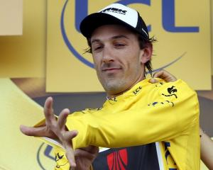 Switzerland's Fabian Cancellara wears the race leader's yellow jersey on the podium after the...