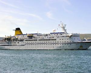The cruise ship Spirit of Adventure, accompanied by tug Otago, heading up the channel toward Port...
