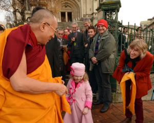 The Dalai Lama greets a young girl in front of St Paul's Cathedral.