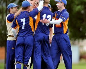The excited bowler, Jack Hunter (shirt No 13), celebrates with his team-mates. Photos by Craig...