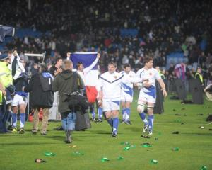 The French team are pelted with bottles as they celebrate their win at Carisbrook on Saturday...