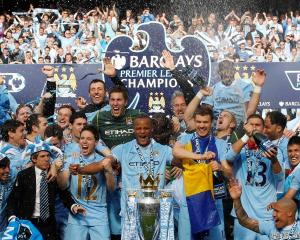 The Manchester City team celebrate winning the English Premier League following their match...