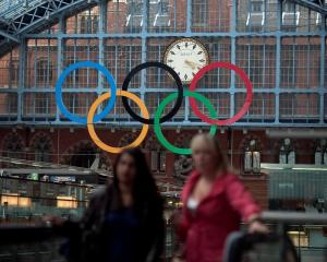 The Olympic Rings are seen as commuters walk in St Pancras Station, home of the Eurostar, in...