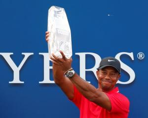 Tiger Woods holds up the trophy after winning the PGA Players Championship golf tournament at TPC...
