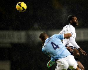 Tottenham Hotspur's Emmanuel Adebayor (R) is challenged by Manchester City's Vincent Kompany....