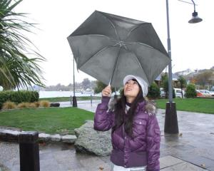 Tourist Sienna Chin, of Taiwan, shelters under her umbrella at Lake Wanaka. Photo by Matthew...