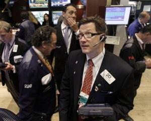 Trader Christopher Forbes watches prices as he works on the floor of the New York Stock Exchange...