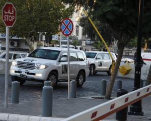 UN vehicles transporting chemical weapons experts return to their hotel in Damascus. REUTERS...