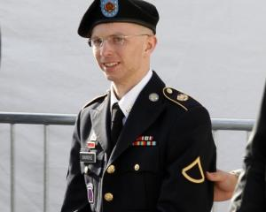 US Army Private First Class Bradley Manning (C) is escorted in handcuffs as he leaves the...