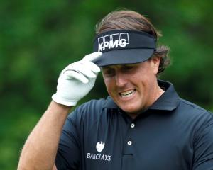US golfer Phil Mickelson reacts to applause after hitting his tee shot on the 11th hole during...