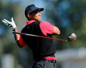US golfer Tiger Woods lets go of his driver on his follow through while hitting off the 9th tee...