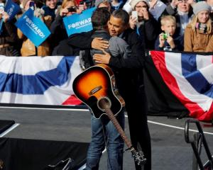 US President Barack Obama (R) hugs singer Bruce Springsteen as he is introduced before he speaks...