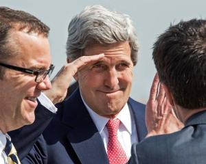 US Secretary of State John Kerry (C) salutes to bid farewell as he prepares to depart from...