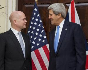 US Secretary of State John Kerry (R) talks with British Foreign Secretary William Hague at...