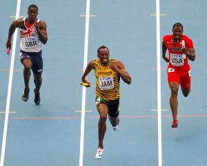 Usain Bolt of Jamaica (C) sprints to the finish line ahead of Dwain Chambers of Britain (L) and...