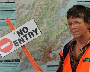 Volunteer Pat Dean with the extra sign she is putting up on Sandfly Bay after a run-in with a...