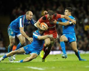 Wales' Jamie Roberts (C) is caught by the Italian defence. REUTERS/Rebecca Naden