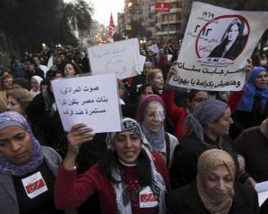 Women shout slogans against Egyptian President Mohamed Morsi and members of the Muslim...
