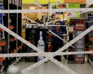 Workers puts tape to close an aisle with hard liquor in a supermarket in Prague. REUTERS/David W...