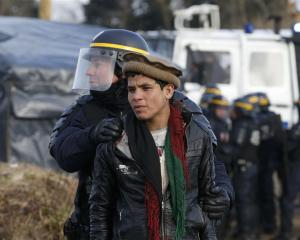 A French CRS riot policeman apprehends a young Afghan during a protest by migrants against the...