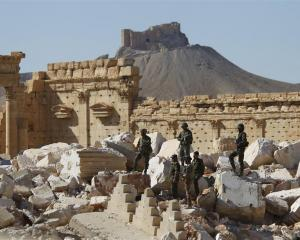 Syrian army soldiers stand on the ruins of the Temple of Bel in the historic city of Palmyra, in...