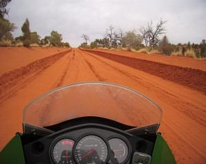 The red dirt of the Australian outback as seen from a motorcycle. Photo by Jenny Longstaff.