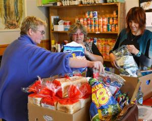 Mosgiel Foodbank volunteers Julie Eaton (left) and Kerrie Russell (right) help foodbank co...