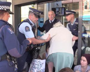 Police help an older woman to negotiate  climate change protesters blocking the entrance to an...