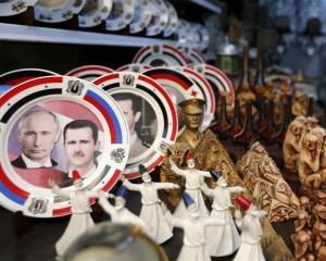 Souvenir plates depicting Syria's President Bashar al-Assad and Russia's President Vladimir Putin...