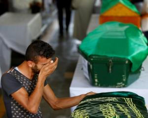 A family member mourns over the coffin of one of the victims during a funeral ceremony in the...