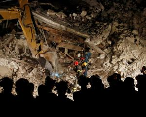Rescuers work in the night at a collapsed house following in Pescara del Tronto. Photo: Reuters