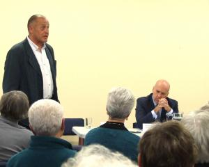 Central Otago mayoral candidate Martin McPherson (left) speaks as Tim Cadogan (centre) and Tony...
