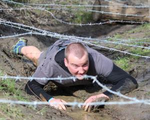 Balclutha man James McDonald crawls cautiously  under barbed wire at  the Balclutha Mud Trudge on...