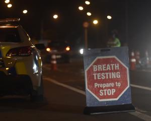 Police officers breath-test motorists at a checkpoint in Kaikorai Valley Rd in Dunedin in an anti...