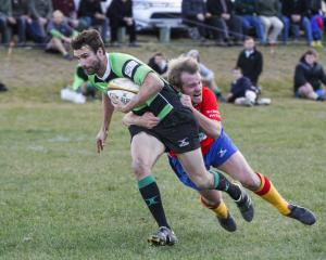Maheno midfield back Craig Smith is tackled by Kurow's Craig Robson during a Citizens Shield club...