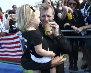 Mahe Drysdale of New Zealand shows his gold medal to his daughter Bronte. Photo: Reuters