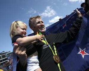 Gold medalist Mahe Drysdale of New Zealand celebrates with his daughter Bronte at Lagoa Stadium, ...