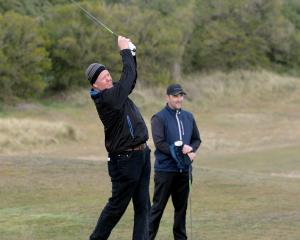 Greg Turner tees off at the first hole, watched by partner Mahal Pearce, during the Otago men's...