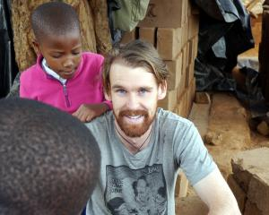 Hamish Garry helps to build a hall in Moshi, Tanzania, watched by local children. Photo: supplied.