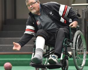 Ken Walker bowls from a wheelchair during the world indoor qualifying singles tournament at the...