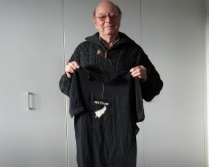 lan Larkins holds aloft the team shirt he was given for the 1956 Olympics held in Melbourne....