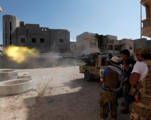 Libyan forces allied with the UN-backed government fire a weapon towards Islamic State militants...