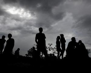 People are silhouetted at the landslide site. REUTERS/Jorge Cabrera