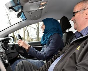 Syrian refugee Manahel Haroara takes a professional driving lesson from Jim Pine in Stuart St,...
